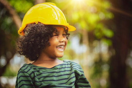 Happy little boy engineer wearing yellow safety helmet hard hat and laughing with happiness. Education and learning concept.