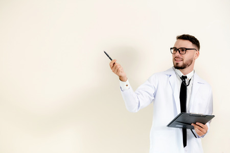 Male doctor points pen at empty copy space while holding a document clipboard in another hand.