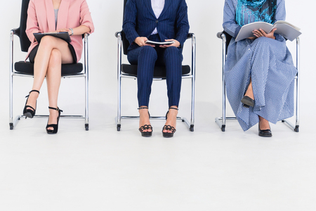 Business people job applicants sitting and waiting on chairs in office. Job application and recruitment concept.