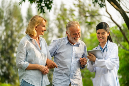Senior couple man and woman talking to young nurse or caregiver in the park. Mature people healthcare and medical staff service concept.