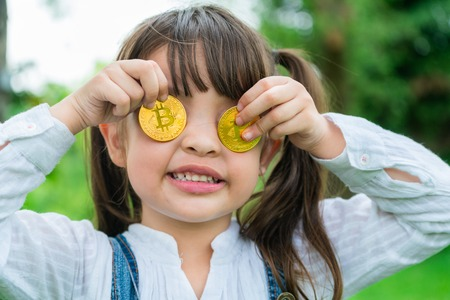 Little girl kid holding bitcoin digital money. Concept of easy bitcoin investing and trading. Foto de archivo