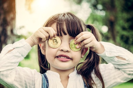Little girl kid holding bitcoin digital money. Concept of easy bitcoin investing and trading. Imagens