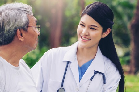 Friendly doctor taking care of senior man in the hospital garden. Medical and healthcare doctor service concept.