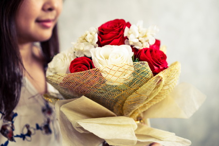 Happy woman gets rose bouquet gift from her boyfriend on Valentines day. Couple love lifestyle concept.