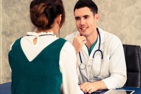 Young doctor examining female patient in hospital office. Medical healthcare and doctor staff service concept. Stock Photo