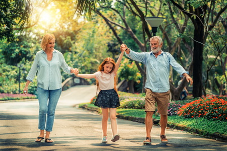 Happy healthy family walk together on path in the park in summer. Concept of family bonding. Stock Photo