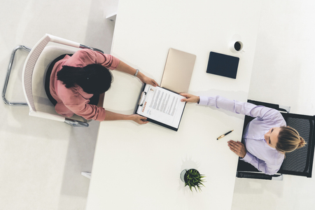 Two young business women in meeting at office table for job application and business agreement. Recruitment and human resources concept. Stock fotó