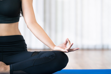 Young woman practicing yoga position in an indoor gym studio. Healthy and wellness lifestyle concept. Stockfoto