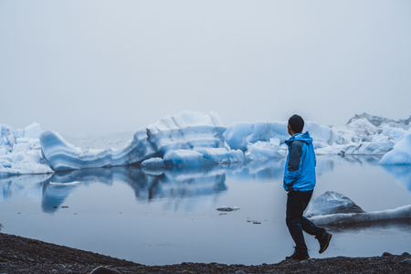 Man traveler travels to Jokulsarlon beautiful glacial lagoon in Iceland. Jokulsarlon is a famous destination in Vatnajokull National Park, southeast Iceland, Europe. Cold winter ice nature. Stock Photo