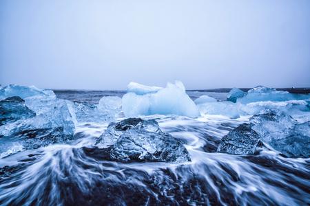 Icebergs on Diamond Beach in Iceland. Frozen ice on black sand beach known as Diamond Beach flows from Jokulsarlon beautiful Glacial Lagoon in Vatnajokull National Park, southeast Iceland, Europe. Фото со стока