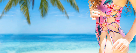 Feliz joven vistiendo traje de baño en el resort de playa de arena tropical en verano para vacaciones viajes vacaciones. Foto de archivo