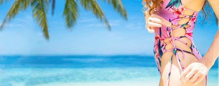 Gelukkige jonge vrouw die zwempak draagt bij tropisch zandstrand in de zomer voor vakantiereizen. Stockfoto