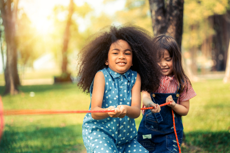 Happy children playing tug of war and having fun during summer camping in the park. Children recreation concept.