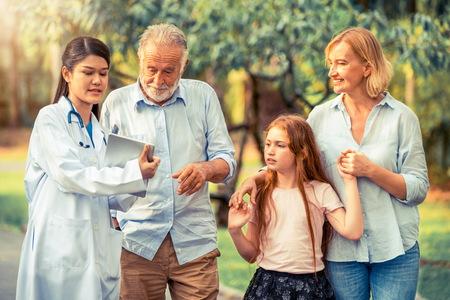 Feliz familia sana y médico hablando en el parque. Concepto de servicio de salud y personal médico de personas.