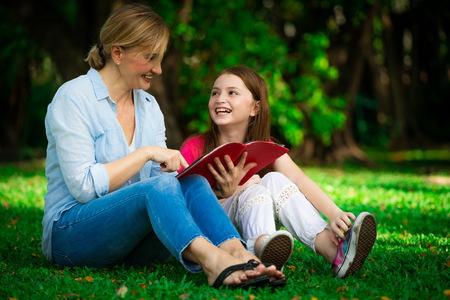 Madre felice rilassata e figlia del bambino nel parco pubblico all'aperto. Genitorialità e concetto di bambino. Archivio Fotografico