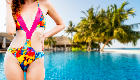 Happy young woman wearing swimsuit at tropical sand beach resort in summer for holiday travel vacation.