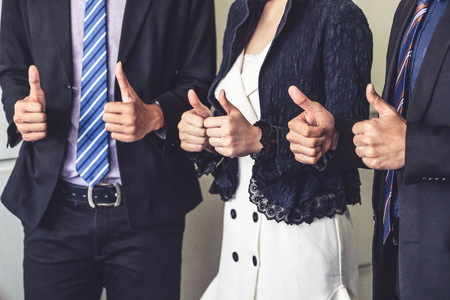 Many happy business people make thumbs up sign join hands together with joy and success. Company employee celebrate after successful work project. Corporate partnership and achievement concept.