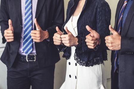 Molti uomini d'affari felici fanno i pollici in su segno si uniscono per mano con gioia e successo. L'impiegato dell'azienda festeggia dopo un progetto di lavoro di successo. Partnership aziendale e concetto di successo.
