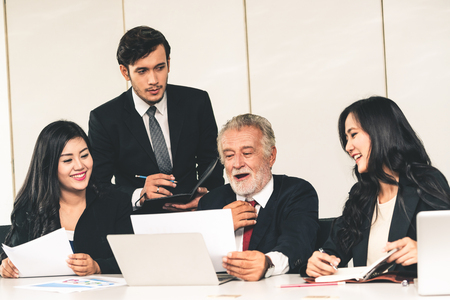 Senior caucasian manager working in office with assistance of young Asian business people and translator in the meeting. Corporate international business and secretary language translation concept.