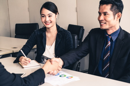 Business people agreement concept. Asian Businessman do handshake with another businessman in the office meeting room. Young Asian secretary lady sits beside him. Stock fotó