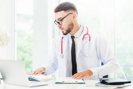 Doktor, der am Laptop am Bürotisch im Krankenhaus arbeitet. Medizin- und Gesundheitskonzept.