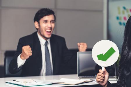 Menedżer ds. zasobów ludzkich zatrudnia kandydata do pracy płci męskiej, który zda rozmowę kwalifikacyjną, siedząc w pokoju biurowym. Szczęśliwa rozmowa kwalifikacyjna OK. Podanie o pracę, rekrutacja i koncepcja zatrudniania pracowników w Azji.