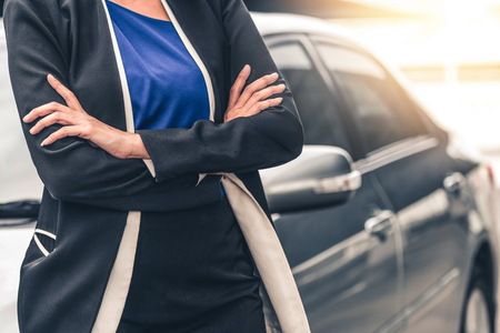 Confident professional business woman standing beside the car. Concept of car rental business and sales occupation.