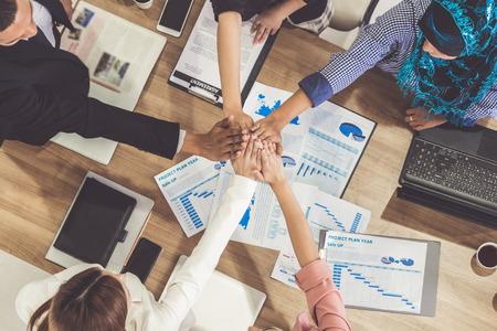 Hommes d'affaires et femmes d'affaires se donnant la main lors d'une réunion de groupe dans une salle de bureau multiculturelle montrant le travail d'équipe, le soutien et l'unité dans les affaires. Lieu de travail de la diversité et concept de travail des personnes d'entreprise. Banque d'images