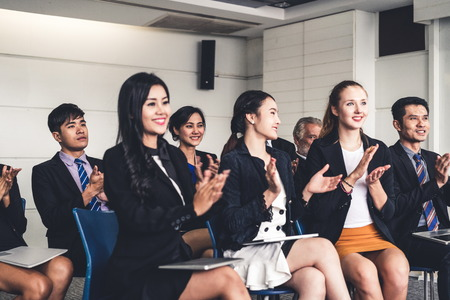 Professional young Asian and Caucasian audience applauding in group meeting presentation from the partnership at the office. Businessmen and businesswomen celebrating the great success achievement.