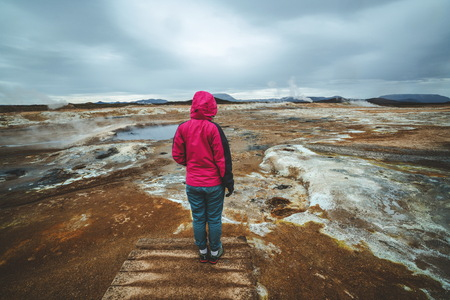Woman traveler travels to Hverir in Iceland. Hverir (Icelandic: Hverarond) is geothermal area in Myvatn. It is a famous destination near Lake Myvatn, Krafla northeastern region of Iceland, Europe.