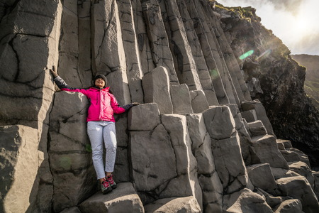Traveler travel to unique volcanic rock formation on Iceland black sand beach located near the village of Vik i myrdalin South Iceland. Hexagonal columnar rocks attract tourist who visit Iceland. Banco de Imagens
