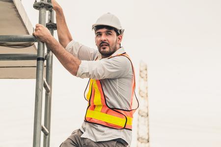 Il muratore o l'ingegnere del giovane salgono la scala sulla cima dell'edificio. Concetto di progetto di ingegneria. Archivio Fotografico
