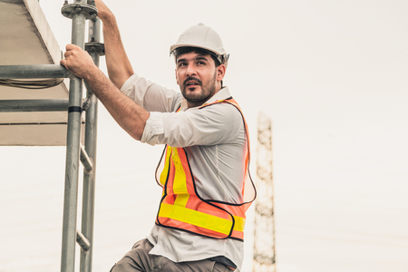 Young man construction worker or engineer climb ladder on the building top. Engineering project concept. Stock Photo