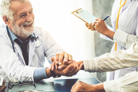 Senior male doctor talking to elder man patient in the hospital office. Medical healthcare and doctor staff service concept. Stock Photo