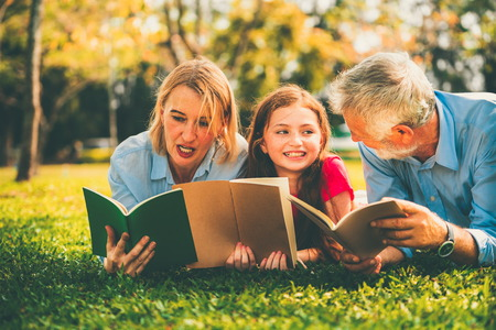 Happy family read books together and lying on green grass in public park.