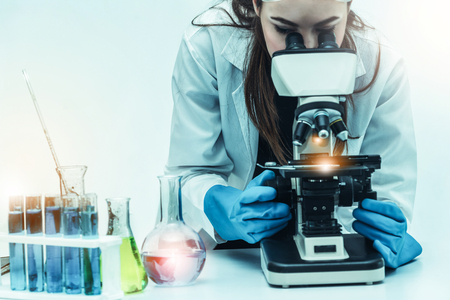 Young woman scientist working in chemical laboratory and examining biochemistry lab sample.