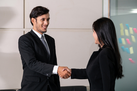 Business people agreement concept. Businessman and Asian businesswoman do handshake in the office. Stok Fotoğraf - 119286380