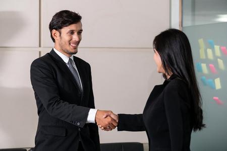 Concetto di accordo di uomini d'affari. L'uomo d'affari e la donna d'affari asiatica si stringono la mano in ufficio.