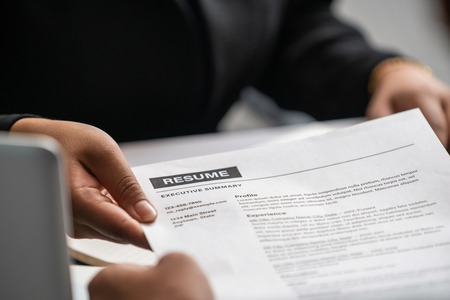 Close up view of employee candidate hands CV resume document to the interviewer HR human resources department manager at the interview room. Job application, recruit and labor hiring concept.