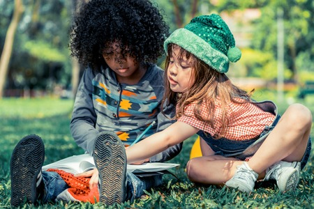 School boy and girl reading book together in the park. Education and friends concept. Stock Photo