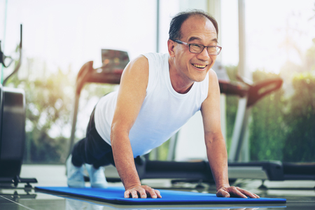 Senior man push up in fitness gym. Mature healthy lifestyle. Stockfoto