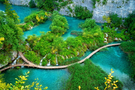Beautiful wooden path trail for nature trekking with lakes and waterfall landscape in Plitvice Lakes National Park Фото со стока