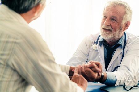 Senior male doctor talking to elder man patient in the hospital office. 版權商用圖片