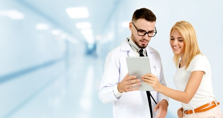 Doctor talking to patient in the hospital. The happy patient is listening to explanation from the doctor.