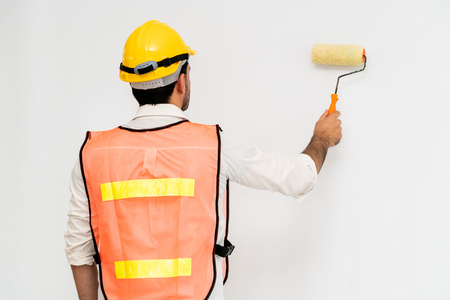Construction worker painting the wall.