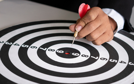 Businessman leader aiming at mission target. Concept of challenge in business marketing bullseye and intelligent customer reach. The dart is the strategy or skill. The dartboard is the project goal.