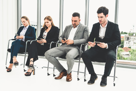 Businesswomen and businessmen using mobile phone while waiting on chairs in office for job interview.