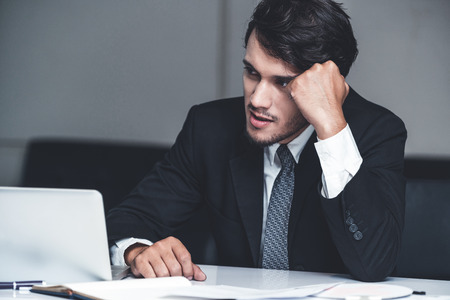 Unhappy young man, businessman feels stress at the office because of economic crisis and awful company loss.