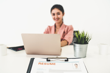 Resume or CV (curriculum vitae) document paper sent to businesswoman from human resources department sitting at table in office. Job application and hiring concept.