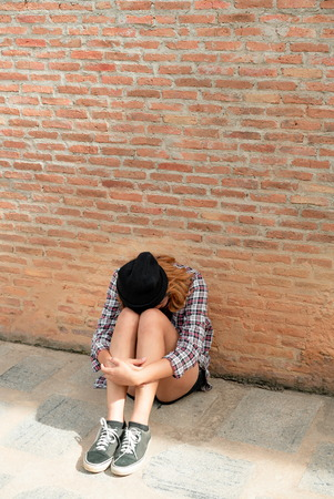 Depressed teenage woman feeling sad alone against brick wall in old town. Education and family failure concept.